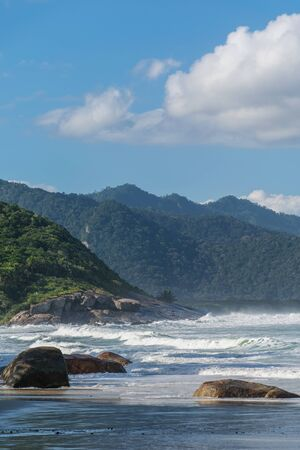 Panorama of a natural environment with the sea waves hitting against wide rocks and a great mountain with tall trees in the background at Costao do demo, Ilha Grande, Rio de Janeiro