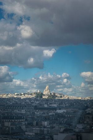 Dramatic view of the city landscape being taken over by shadow while the famous landmark of the Basilica of Sacre Coeur shines in the sunlight at the Montmartre district in Paris, France