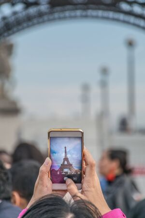 Curious and interesting image of a picture within a picture of a tourist taking an upwards photograph of the Eiffel tower in a common smartphone with blurred background in Paris, France