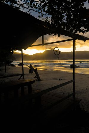 High contrast view of a stunning sunset through the mountains and by the beach with the sunlight reflecting in the sea and a tent by the sand with a wooden table and a dream catcher hanging outside Imagens