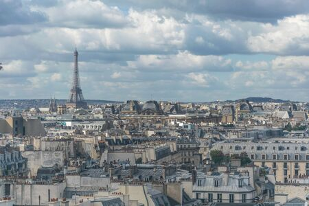 Skyline view of the architecture of the conglomerate of buildings of the urban setting of Paris, France, with the famous eiffel tower landmark in the background during the daylight Zdjęcie Seryjne - 129721327