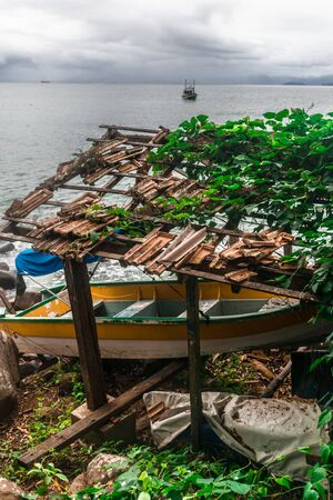 Curious perspective of a white, yellow and green boat kept under a broken roof with sparse roof tiles being taken over by the vegetation nearby and a small single boat by the sea under a cloudy sky