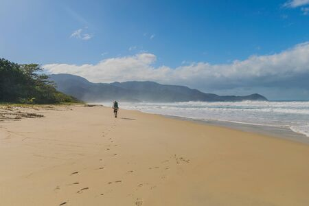 Horizontal perspective of a sunny and tropical landscape with a traveler wearing a hat leaving footprints behind in the sand by the beach with natural vegetation and mountains in the background 写真素材