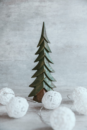 Beautiful and modern christmas composition on wooden background. White baubles, handmade christmas tree. Copy space, greeting card.