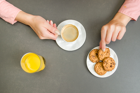 Woman hand having breakfast, coffee, orange juice, cookies.