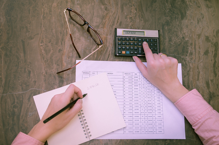 Great concept of finance, woman hand working, calculating, tables, financial calculator, writing on notepad.