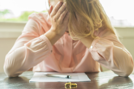 Great concept of divorce, end of relationship, sad young woman, divorce agreement, with hands in the face. Stock Photo