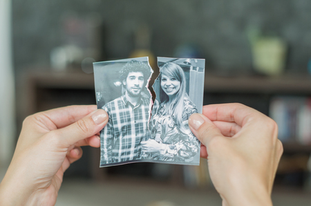 Great concept of divorce, betrayal, separation, woman hand ripping photo of the couple. Banco de Imagens