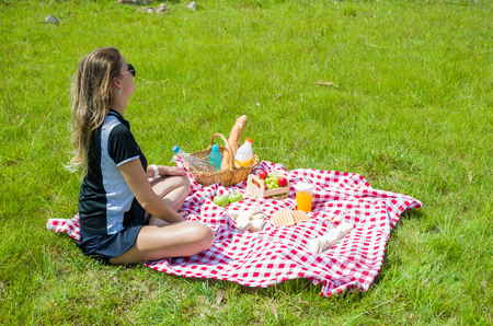 Young woman doing picnic on green lawn with beautiful view Stock Photo