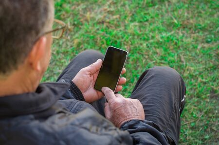 Close up of a wrinkled finger touching the smartphone, old man uses technology. Internet. Imagens - 98538423