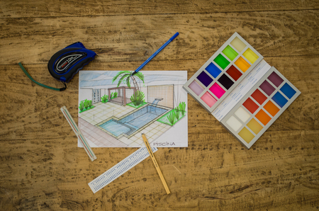 Objects of designer, base plant, hard hat, ruler, color chart and various objects on wooden table.