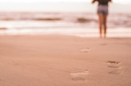 Woman walking on the beach, footprints in the sand.