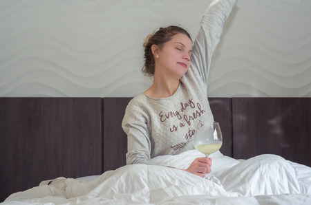 Young blonde woman stretching on bed with glass of wine in hand, waking up happy.