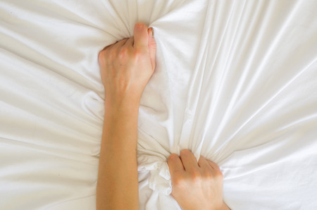 Hand orgasm of woman on white bed, Hand of female pulling white sheets in ecstasy, feeling and emotion concept