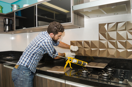 Man renovating, renovating the kitchen, installing tile on the wall. Standard-Bild
