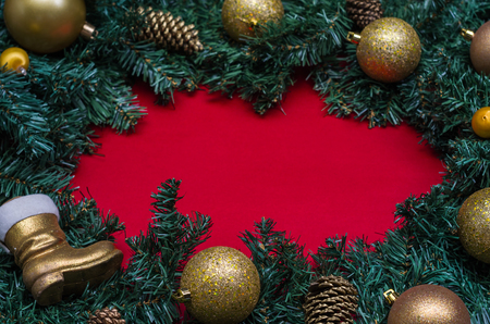 Background with Christmas theme, pine leaves on the edges of red paper and decorative objects.