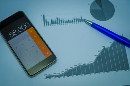 Smartphone, pen, graphs, calculator, credit card and Brazilian money (real), finance concept, home economics. Imagens