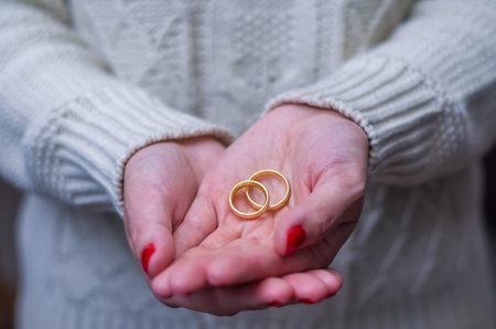 Great concept of divorce woman hand with two gold wedding rings in hand.