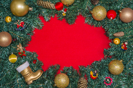 Background with Christmas theme, pine leaves on the edges of red paper and decorative objects. Imagens