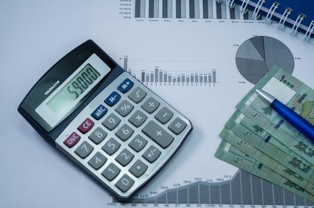Laptop, coffee cup, pen, calculator, graphs and money Lebanese pound, finance concept, home economics.