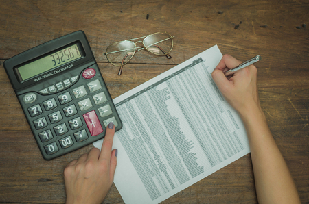 Woman hand calculating yields, calculator and chart