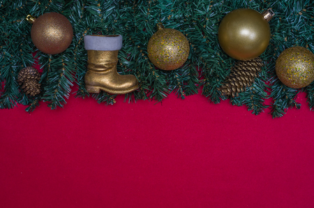 Texture with Christmas theme with green leaves, decorative objects and red background. With copy space. Imagens
