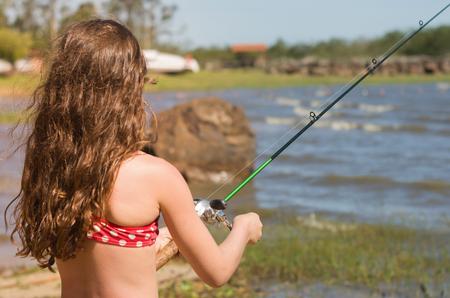 Child fishing in pond, lake.