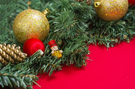 Texture with Christmas theme with green leaves, decorative objects and red background. With copy space.