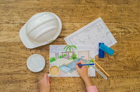 Engineer working, hand of working designer, floor plan, hard hat and sundry objects.