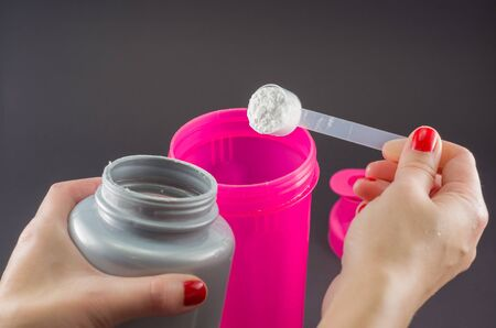 Sport, fitness, healthy lifestyle and people concept - close up of women with jar and bottle preparing protein shake Stock Photo