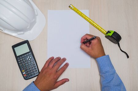 Great background with engineering theme, knolling of engineering objects with hand and copy space on white sheet.