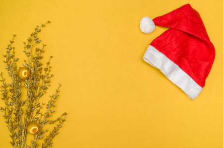 Christmas background with Santa hat, decorative objects and yellow background. With copy space.