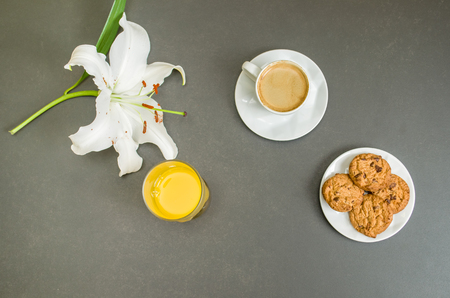 Breakfast from above with espresso, flower, juice of lajanra and cookies on gray table for various backgrounds.