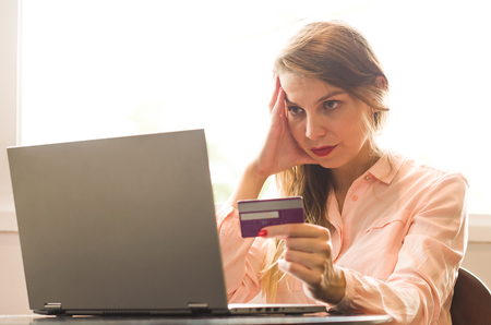 Great concept of online payment, purchase over the internet, woman buying over the internet using a laptop, credit card in hand. Imagens