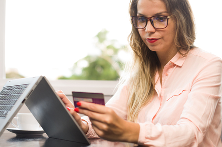 Great concept of online payment, purchase over the internet, woman buying over the internet using a laptop, credit card in hand.