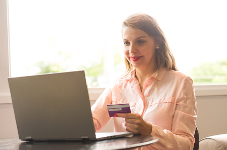 Young blond caucasian woman shopping on the internet, credit card in hand.