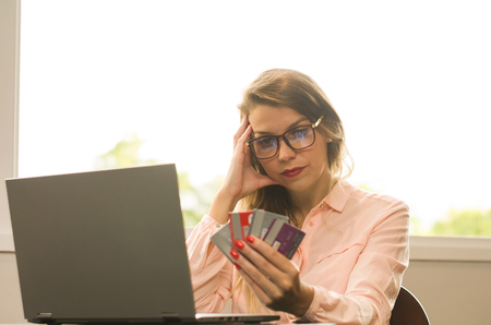 Young blond Caucasian woman worried to pay electronic bills, with several credit cards in hand.