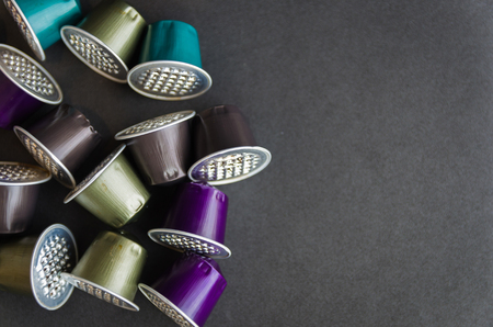 Colorful espresso coffee capsules used on black background, recycling, environment.