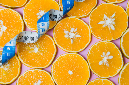 Background for healthy eating concept, beautiful texture of orange slices on pink background with measuring tape 免版税图像