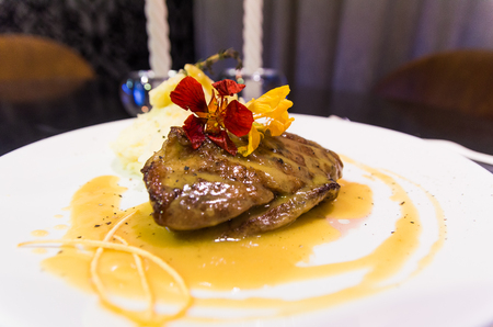 Duck breast with orange sauce on plate decorated with flowers.