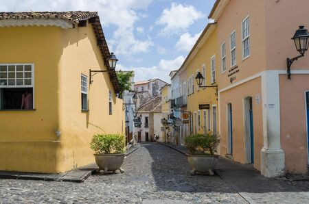Bright sunny view of the historic tourist center of Pelourinho, Salvador da Bahia, Brazil featuring colorful colonial architecture on a broad cobblestone hill