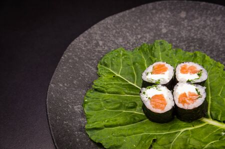 Perfect sushi, traditional Japanese cuisine. Delicious hossomaki on the decorated plate, black background. Stok Fotoğraf