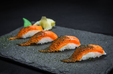 Perfect sushi, traditional Japanese cuisine. Delicious salmon kiguiri on the decorated plate, black background.