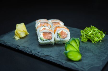 Sushi, traditional Japanese cuisine. Delicious Uramaki on decorated plate, black background.