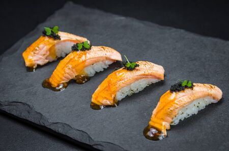Perfect sushi, traditional Japanese cuisine. Delicious salmon kiguiri with capellin roe (caviar) on the decorated plate, black background. Stok Fotoğraf