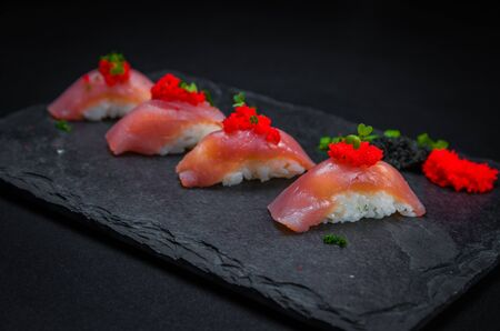 Perfect sushi, traditional Japanese cuisine. Delicious tuna kiguiri with capellin roe (caviar) on the decorated plate, black background.