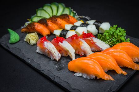 Sushi, traditional Japanese cuisine. Several delicious sushi on the decorated plate, black background. Group of sushi, Urakami, Nigori, Sushi jow, sashimi, tekamaki, etc ... Stok Fotoğraf