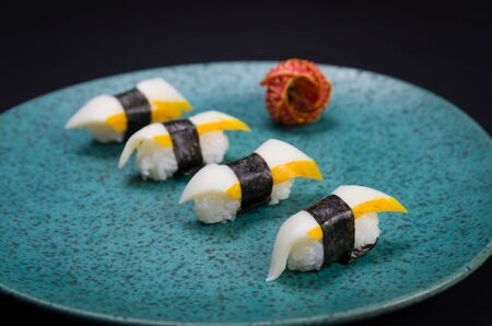 Sushi, traditional Japanese cuisine. Delicious Hadock Tako sushi on decorated plate, black background. Stok Fotoğraf