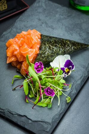 Sushi. Traditional Japanese cuisine, premium salmon Temaki decorated in an elegant setting. Vertical photo. Stok Fotoğraf