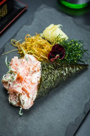 Sushi. Traditional Japanese cuisine, premium salmon Temaki with cream cheese decorated in an elegant setting. Vertical photo.